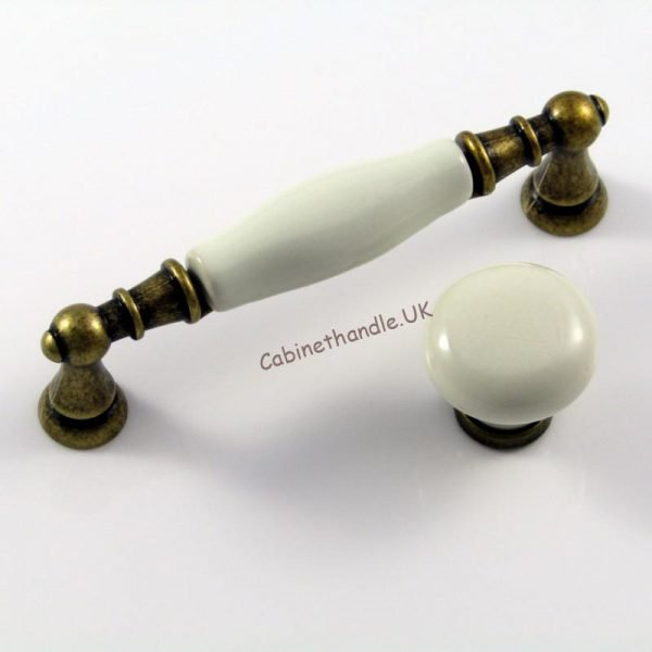 set of two porcelain cabinet pulls made of smooth ivory porcelain and metal finish in old brass colour