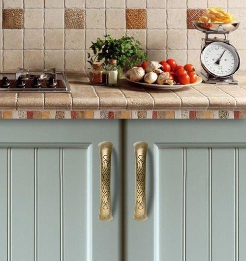 brass pull handles on mint kitchen doors